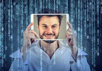 Happy man holding tablet with his face displayed on a screen isolated on binary code background