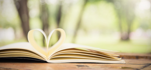 Love, valentine's day or reading concept with heart shaped book on bokeh background, copy space, horizontal banner