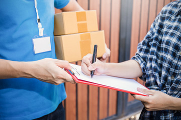 Close up woman hand appending receive sign signature after accepting a delivery of boxes from delivery man, sign and receive delivery concept