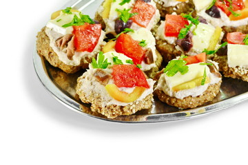 Delicious Appetizer Canapes with pheasant pate, cheese, paprika and tomatoes Isolated over White.