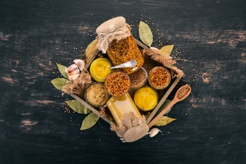 A set of mustard in a wooden box. Spices On a black wooden background. Top view. Copy space for your text.