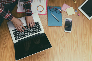 Hands of woman working on laptop, a smartphone and a cup of coffee and other accessories on wood floor.Top view.