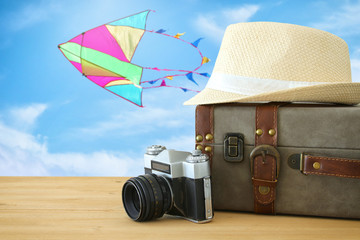 traveler vintage luggage, camera and fedora hat over wooden table infront of blue sky and colorful kite. holiday and vacation concept.