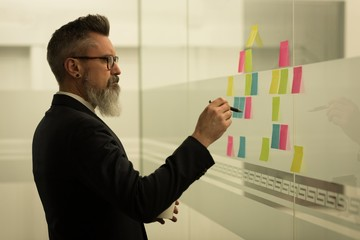 Business executive writing on sticky notes