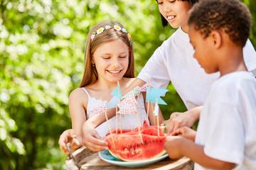 Kinder essen Melone bei Kindergeburtstag