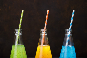 Three multicolored drinks in the bottles on the dark background.
