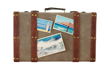 Image of old vintage luggage with vacation photos isolated on white.