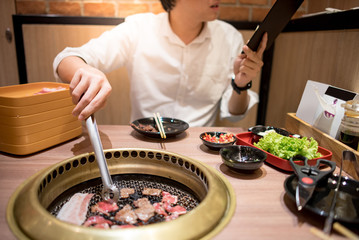 Young Asian man eating Korean Barbecue buffet looking menu while grilling beef for the next order in the restaurant