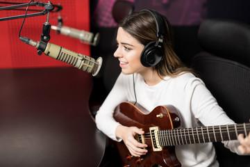 Woman musical artist performing live at radio studio