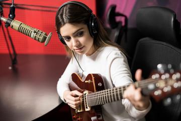 Female singer playing music in radio station