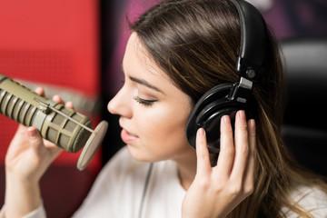 Latin female singer singing at radio station