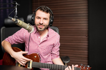Male singer broadcasting a song live at radio station