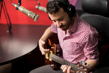 Music artist playing guitar in radio show