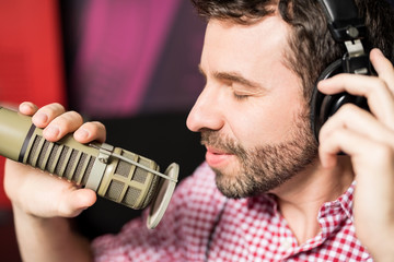 Hispanic young man recording a song in radio studio