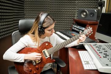 Female guitarist composing music in studio