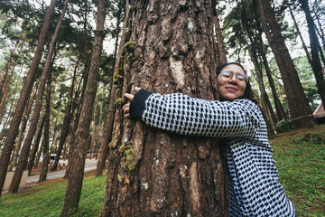 Asian woman hugging big pine tree in the forest.