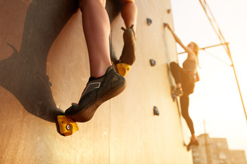Close up view of woman feet in climbing shoes on artificial rock wall on sunset. Two active sporty women compete on speed bauldering championship outdoors.