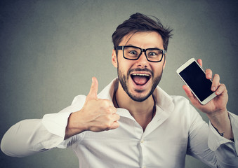 Happy man showing thumb up with phone