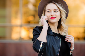 Blonde woman in black hat and leather jacket using the mobile phone.