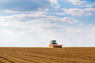 Wall Mural - Farmer seeding, sowing crops at field. Sowing is the process of planting seeds in the ground as part of the early spring time agricultural activities.