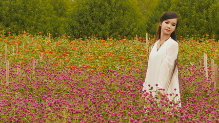 Vietnamese girl with long black hair standing in a plantation purple flowers