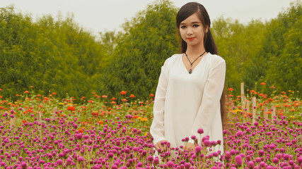 Vietnamese girl with long black hair standing in a plantation purple flowers. Vietnam.