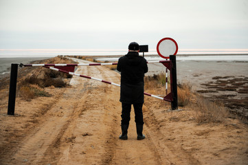 Man stands on road in front of closed gate and restrictive traffic signs. Salt Lake Elton
