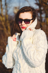 Pretty young stylish woman posing in a trendy fashion coat walks in the park on a sunny winter day