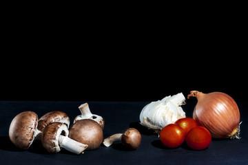 Champignon, Zwiebel Tomaten,  und Knoblauch auf einer Schiefertafel