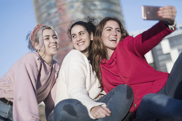 Three happy best girlfriends outdoors making selfie on smartphone.