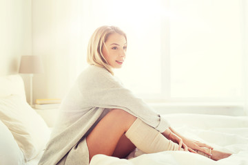 Fototapete - rest, sleeping, comfort and people concept - happy young woman sitting in bed at home bedroom