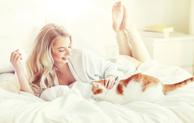 Fototapete - pets, morning, comfort, rest and people concept - happy young woman with cat in bed at home