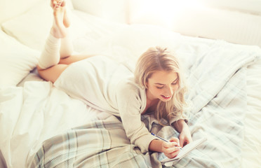 Fototapete - rest, sleeping, comfort and people concept - happy young woman with pen and notebook writing in bed at home bedroom