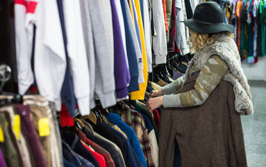 Woman in a hat browsing through clothing in a vintage thrift store