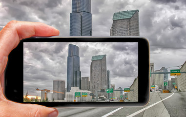 Male hand with smartphone taking a picture of Seattle. Tourism concept