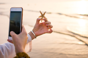Female taking picture of a starfish on the beach