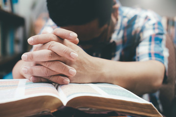 Man praying, hands clasped together on her Bible. Wall mural
