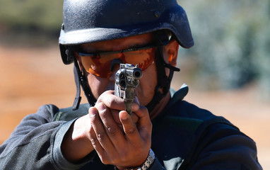 A police officer of the local prison, point at target during a practice session at a shooting military range in Valparaiso