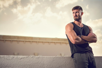 Handsome muscular sportsman with crossed hands looking away outdoors. Wall mural
