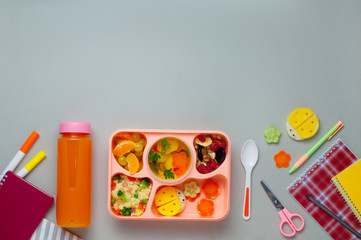 Lunch box with orange juice and notebooks on grey background