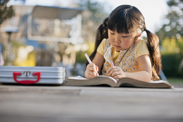Young girl coloring in a coloring book.