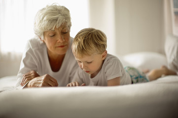 Mature woman and grandson lie on their fronts on a bed side by side while looking down.