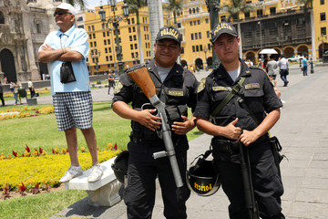 Peruvian police holding riot guns pose for a picture near Government Palace in Lima