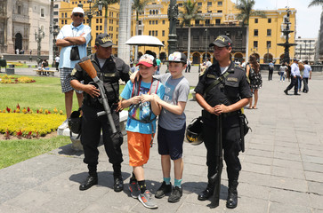Peruvian police holding riot guns pose with children for a picture near Government Palace in Lima
