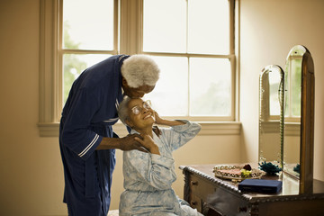 Senior man leans over a senior woman  to kiss her on the forehead as she sits at a dressing table.