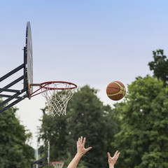 Hands of player throwing basketball ball into basket. Street basketball game. Basketball shield, Basket and ball on background of sky, sport, active lifestyle