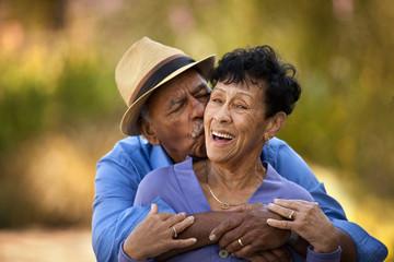Senior man hugging and kissing his wife.