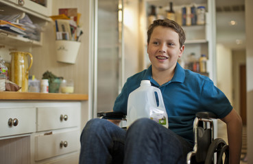 Teenage boy sitting in a wheelchair with a plastic bottle of milk.