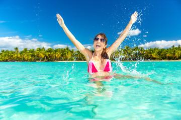 junge hübsches mädchen im bikini im seichten meer vor einer insel mit palmen in der karibik