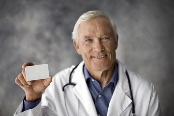 Smiling doctor holding up a white card.